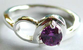 Sterling silver ring with carved-out double knot pattern holding a rounded amethyst stone at center